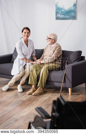 Geriatric Nurse Holding Hands With Aged Man Sitting On Sofa At Home