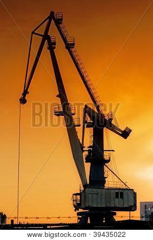 Silhouette of harbor crane at sunrise.