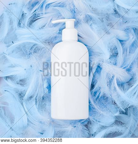 Spa Cosmetic Product, White Bottle, Branding Mock Up, Top View On Blue Feathers Background. Flat Lay