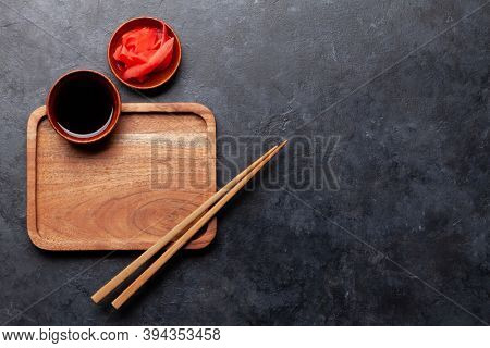 Wooden plate and chopsticks for your sushi and maki. Japanese food menu backdrop. Top view flat lay with copy space
