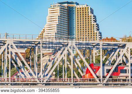 Sochi, Russia - October 08, 2020: Passenger Train Moves Through The Bridge On The Prestige Hotel Bac