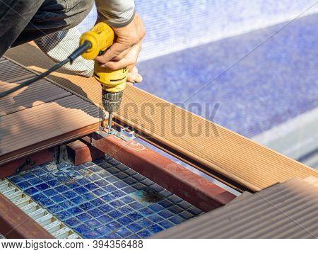 Man Assembling Composite Deck Using Cordless Screwdriver.