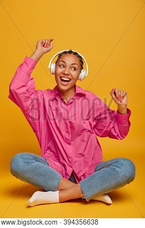 Cheerful Ethnic Millennial Girl Concentrated On Music, Expresses Positive Emotions, Moves With Rhyth