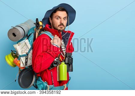 Photo Of Male Vacationist Has Active Rest, Carries Rucksack With Map, Rolled Up Rag, Wears Casual To