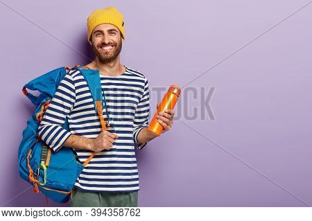 Satisfied Unshaven Man Holds Thermos And Big Rucksack, Ready For Adventurous Trip, Smiles Gladfully,