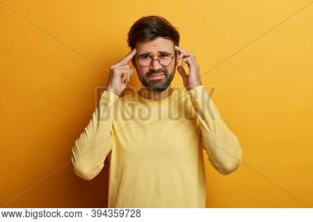 Dissatisfied Man Thinks Intensely, Touches Temples With Index Fingers, Smirks Face, Suffers From Unb