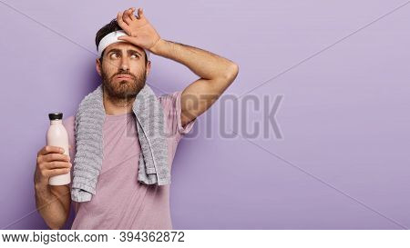 Exhausted Athlete Man Feel Thirsty And Tired After Hard Cardio Workout, Wipes Sweat On Forehead, Hol