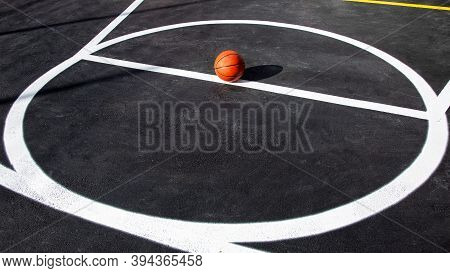 Orange Striped Basketball Ball Stands In Circle On The Marking Playing Field With Asphalt Tarmac, Sp