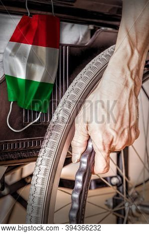 Elderly Person In Wheelchair At Italy Nursing Home With Hanging Italian Flag Face Mask. Concept Of C