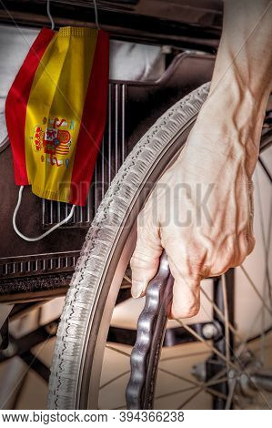 Elderly Person In Wheelchair At Spain Nursing Home With Hanging Spanish Flag Face Mask. Concept Of C