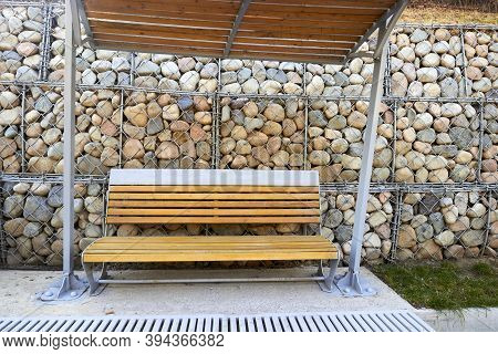 Wooden Bench With Canopy Against Gabion Wall