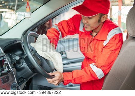 Male Car Cleaner Wearing Red Uniform Wipes The Steering Wheel