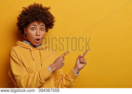 Intrigued Surprised Adult Ethnic Woman With Afro Hairstyle Points At Upper Right Corner, Shows Sign