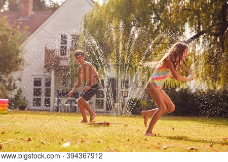 Children Wearing Swimming Costumes Having Fun In Garden Playing In Water From Garden Sprinkler