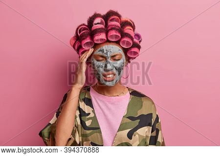 Stressful Young Woman Wears Beauty Mask And Hair Curlers, Suffers Migraine, Clenches Teeth And Close