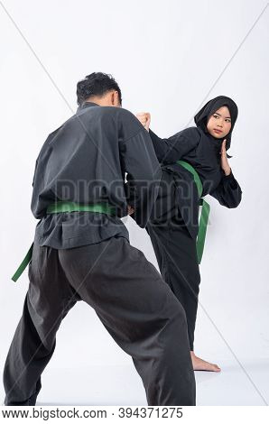 Back View Of A Man Wearing A Pencak Silat Uniform Standing With A Movement To Block The Kicks Of An