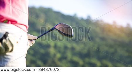 Women Golfer Using Golf Clubs To Help Twist To Warm Up Body Before The Play Game, With Blurred Soft