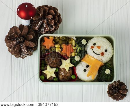 Holiday Lunch Bento Box With Snowman For Kids Over White Background And Pine Ornaments