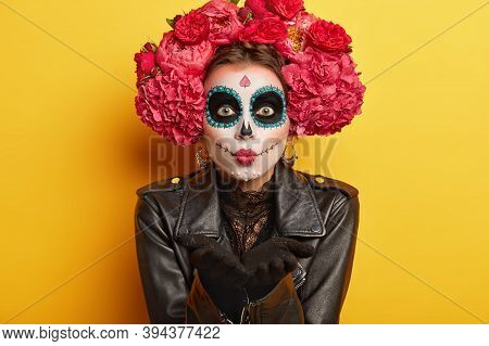 Portrait Of Female Dapper Skeleton Prepares For Mexican Carnival, Blows Air Kiss, Wears Skull Makeup