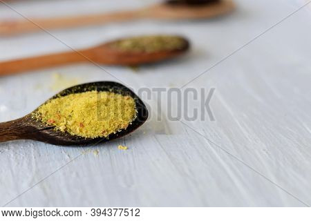Various Spices On Wooden Spoons. Food Ingredients./ Assortment Of Colorful Spices In The Wooden Spoo