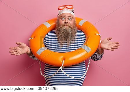Hesitant Doubtful Bearded Man Spreads Hands Sideways, Feels Confused, Wears Swimming Hat, Goggles An