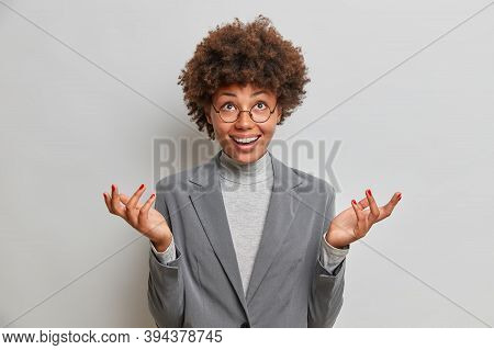 Positive Hesitant Business Lady Speads Palms Clueless, Looks Up At Ceiling, Hesitates Over Choice, D