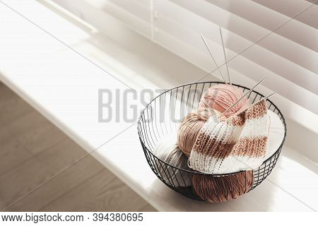 Yarn Balls And Knitting Needles In Metal Basket On Window Sill Indoors, Space For Text. Creative Hob