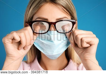 Woman Wiping Foggy Glasses Caused By Wearing Disposable Mask On Blue Background, Closeup. Protective