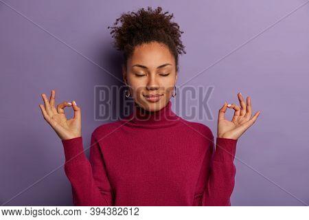 Portrait Of Good Looking Woman Meditates, Keeps Both Hands In Okay Gesture, Keeps Eyes Closed, Pract