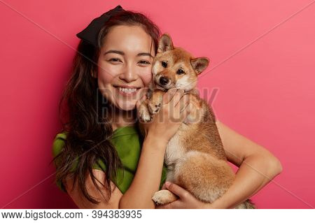 Picture Of Adorable Young Girl With Toothy Smille, Embraces And Makes Photo With Beautiful Obedient