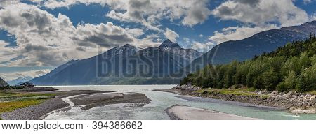 Panoramic Shot Of Yucatania Point And Shallow Skagway River In Skagway, Alaska. Mountains And Cloudy