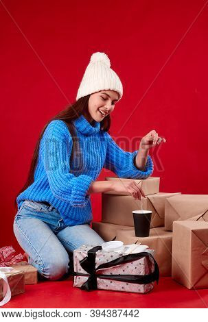 Girl In A Hat Pours Sugar In Coffee Red Background.