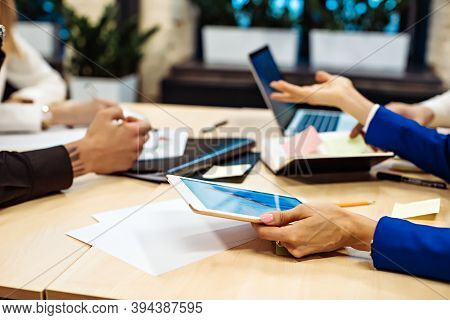 Close Up Of Hands Of Businesspeople Working At Desk In Office