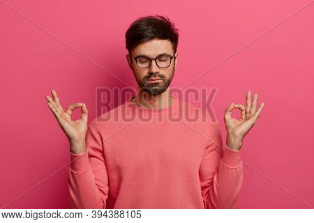 Patience, Calmness And Meditation Concept. Peaceful Relieved Bearded Young Man Practices Yoga Exerci