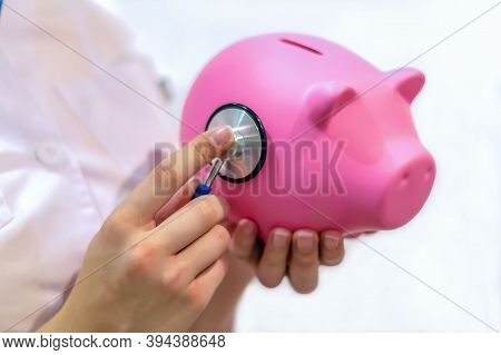 Close-up Of A Young Female Doctor In A White Medical Coat Holding A Cute Pink Piggy Bank And Checkin