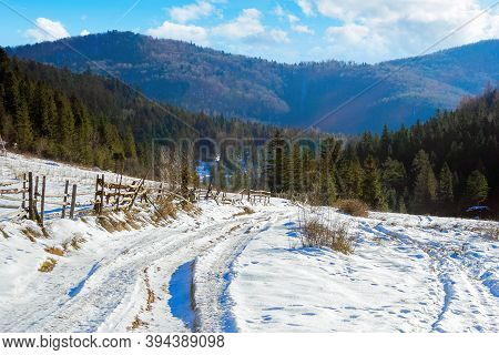 Carpathian Countryside On A Sunny Winter Day. Beautiful Mountainous Rural Landscape. Fence Along The