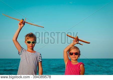 Happy Boy And Girl Flying Toy Planes On Beach Vacation