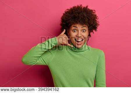 Joyful Afro American Woman Makes Call Me Back Gesture, Has Optimistic Face Expression, Wears Green T