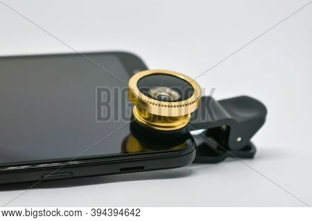 Black Smartphone With Lens On Clip Isolated On White. An External Wide-angle Lens And Clip Are Suppl