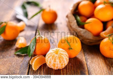 clementine and leaf on wood background