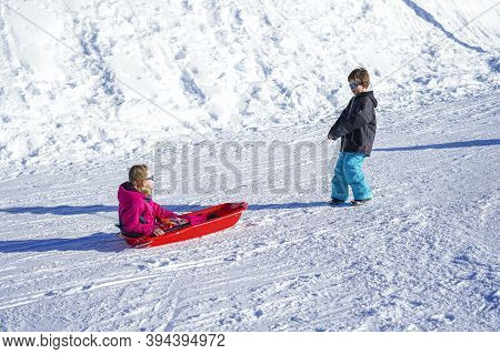 Brother Pulling His Sister Kids Toboggan Sled Snow. Little Girl And Boy Enjoying Sleigh Ride. Child