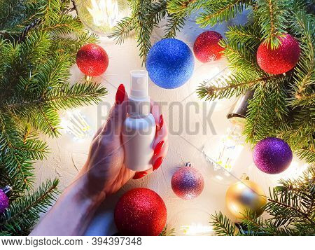 Unbranded White Plastic Spray Bottle, Female Hand With Red Nails, Christmas Balls And Fir Tree On Gr