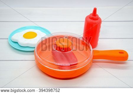 Still Life Of Children's Toy Plastic Dishes: Frying Pan With Lid, Sausages, Fried Eggs On Plate, Ket