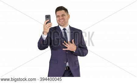 Young Businessman Using Smartphone To Videocall To Business Partner While Walking On White Backgroun