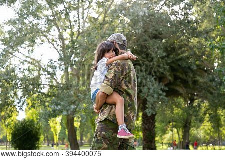 Caucasian Dad In Army Uniform Embracing Daughter. Middle-aged Father Standing In City Park. Cute Gir