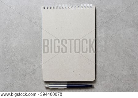 A Spring Notebook With A Sheet Of Craft Paper A5 With A Ballpoint Pen On Light Grey Concrete Backgro