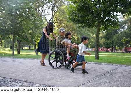 Disabled Man In Military Uniform Walking With Wife And Kids In Park. Pretty Mother Pushing Wheelchai
