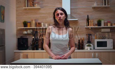 Traumatised Woman Sitting In The Kitchen Looking At The Camera. Violent Aggressive Man Abusing Injur
