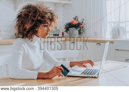 Dark Skinned Lady With Kinky Hair In White Typing On Keyboard Holding Blue Credit Card Enjoys Shoppi