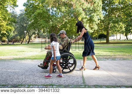 Smiling Military Man Walking With Family In City Park. Long-haired Mother Pushing Wheelchair. Little
